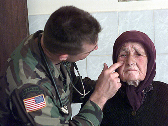 A US Army physician's assistant provides medical assistance to an elderly Serbian woman in Kosovo.