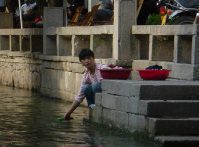 A woman washing clothes in a canal, Zhouzhang Jiangsu.