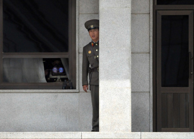 DPRK Guard peers out from behind a granite pillar.