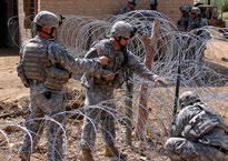 United States soldiers build a security fence in Muehla, Iraq.