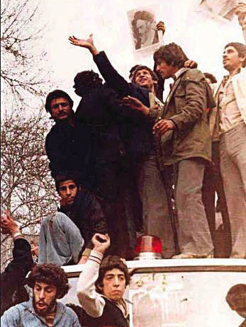 Protesters hold up images of Ayatollah Khomeni during the 1979 revolution
