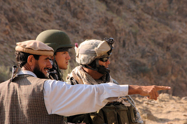 A US Army Sergeant receives road activity reports from a local and his interpretor in Nuristan Province, Afghanistan.