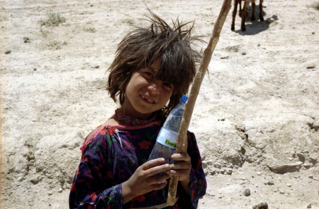 A Kuchi child holds a water bottle, something many of the remote villages of Afghanistan would not have access to otherwise.