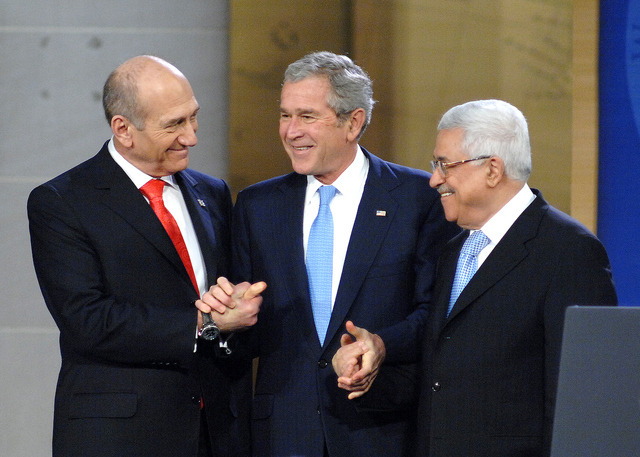 Israeli Prime Minister Ehud Omert, left, President George W. Bush, and Palestinian President Mahmoud Abbas shake hands at the Annapolis Conference, November 2008