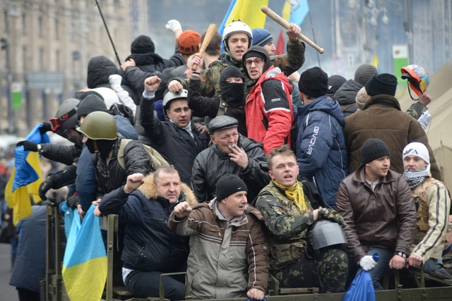 Pictured opposite, protestors celebrate after a compromise deal is reached between parliament and President Yanukovych.