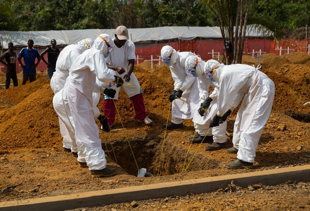 Health workers in West Africa lower an ebola victim into the ground in a safe burial process